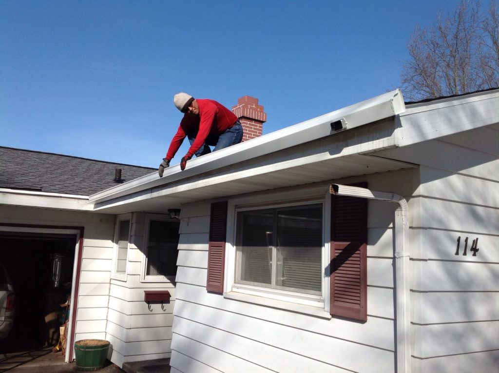 man fitting Aluminum Guttering to house
