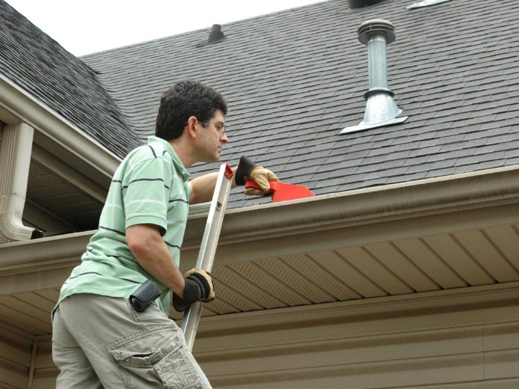 man inspecting seamless guttering